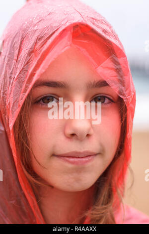 Portrait of pretty teenager girl in wet red raincoat under the rain - Stock Photo