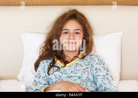 Just awake pretty teenager girl with funny emotion face and wild hair on bed - Stock Photo