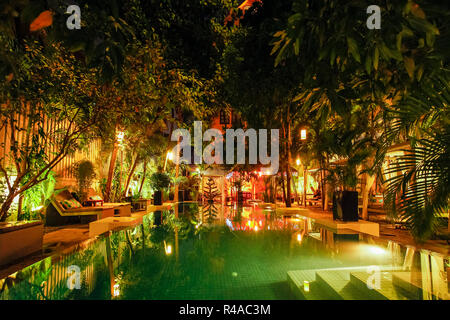 Leafy patio & swimming pool of the Blue Lime boutique hotel at night. An oasis in the city centre; Street 19, Phnom Penh, Cambodia - Stock Photo