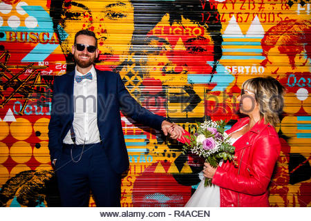 Couple of newlyweds pose in front of a graffitied metal blind - Stock Photo