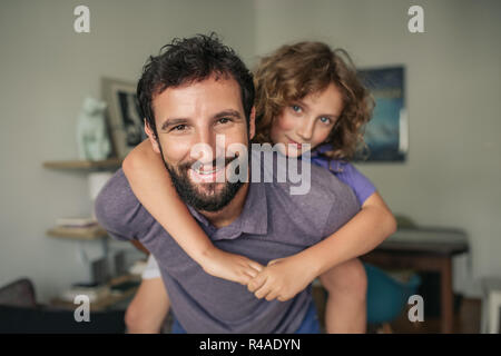 Smiling dad giving his son a piggyback at home - Stock Photo