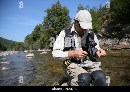 Fly fisherman choosing artificial fly for fishing rod - Stock Photo