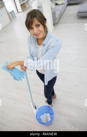 Young housekeeper standing with mopping equipment - Stock Photo