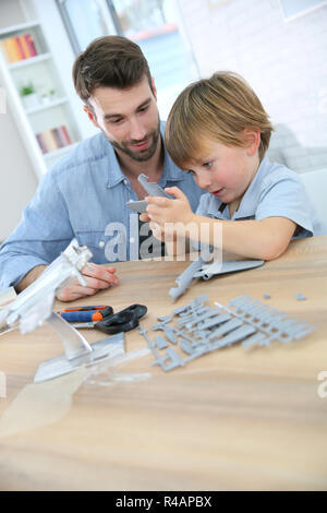 Father and son assembling airplane mock-up - Stock Photo