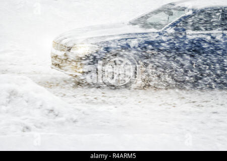 Car rides through a snowstorm. Limited vision on the road. Blizzard - car traffic in bad weather conditions - Stock Photo