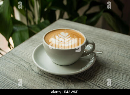 A cup of coffee with beautiful latte art on a grey wooden table in a cafe. - Stock Photo
