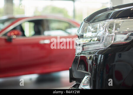 Close up of headlight of amazing black big car for people from premium class. Colorful vehicle standing in luxury salon and waiting for buyers. On background red new wonderful auto. - Stock Photo