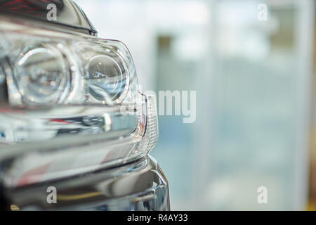 Crop of isolated headlight of big powerful black car. Close up of front part of new expencive vehicle standing indoor. Concept of auto sellings and luxury car salon advertismet. - Stock Photo