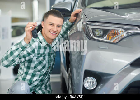 Attractive blonde client choosing car and squatting near luxury one. Close up of handsome young owner of grey big auto holding his hand on it. Happy smiling driver buying vehicle and showing key. - Stock Photo