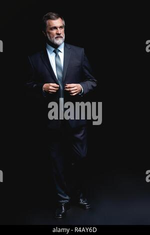 Full length portrait of Mature business man wearing formal suit standing on black background. - Stock Photo
