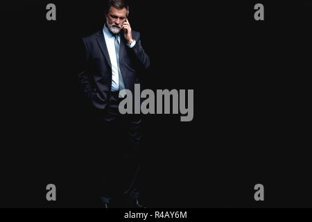 Portrait of a successful businessman on phone against black background. - Stock Photo