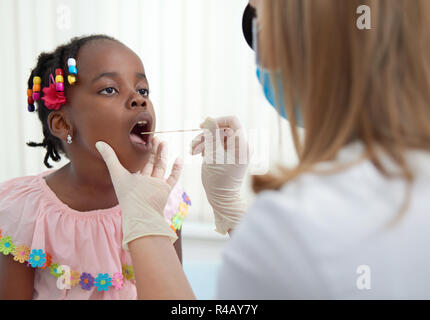 Little african girl on consultation in ENT doctor with opened mouth. Physician in white rubber gloves examining throat of young patient. Specialist holding tool for diagnosis. - Stock Photo