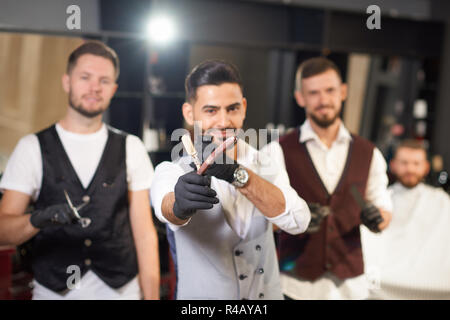 Selective focus of straight razor in hands of stylish hairdresser in vintage barber shop. Qualified male barbers in uniform and protective gloves looking at camera and posing at background.  - Stock Photo