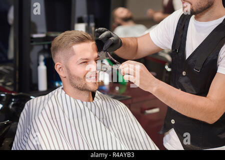 Smiling man sitting on chair in barber shop while barber in protective gloves removing black mask from face of client. Handsome man doing cleaning procedure against dots. Concept of care. - Stock Photo