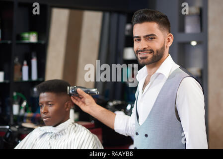 Front view of stylish barber in white shirt and waistcoat looking at camera, posing and smiling in barber shop. Male hairdresser doing trimming hair with clipper to customer sitting at background. - Stock Photo