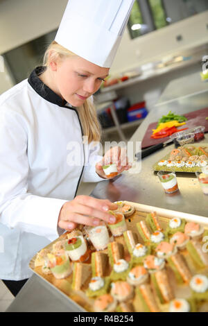 Young caterer preparing tray of appetizer - Stock Photo