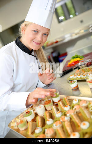 Young caterer preparing tray of appetizers - Stock Photo