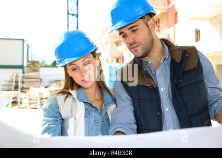 Engineers on building site reading blueprint - Stock Photo