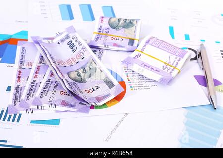 Picture of new Indian Currency Rupees with chart paper and pen. - Stock Photo