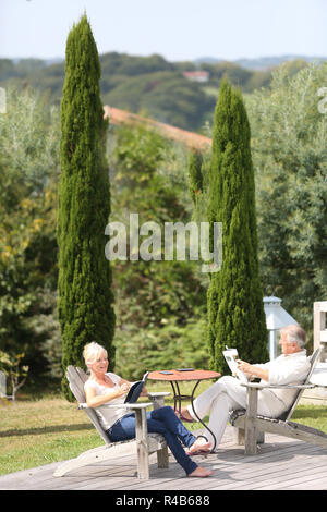 Senior couple in backyard reading book in deckchairs - Stock Photo