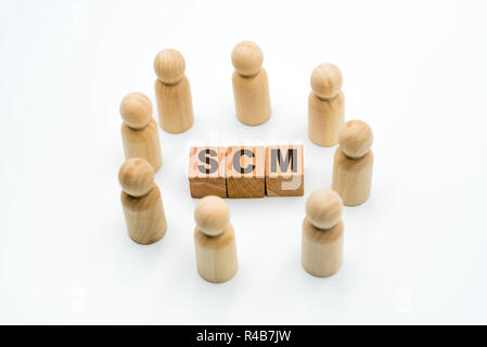 Wooden figures as business team in circle around acronym SCM Supply Chain Management, isolated on white background, minimalist concept - Stock Photo