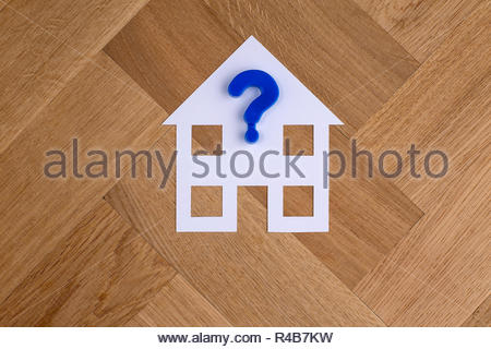 White paper house symbol on wooden floor background with blue plastic question mark - Stock Photo
