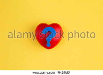 Red plastic heart symbol with blue plastic question mark on top on yellow background - Stock Photo