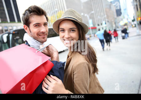 Portrait of cheerful couple doing shopping in Manhattan - Stock Photo