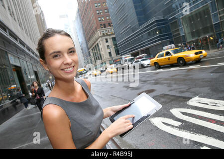 Businesswoman with tablet waiting for a taxi cab in NYC - Stock Photo