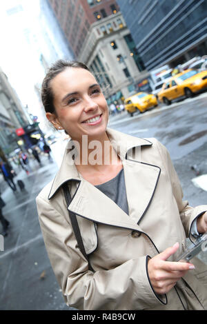 Businesswoman standing in a street of Manhattan with tablet - Stock Photo