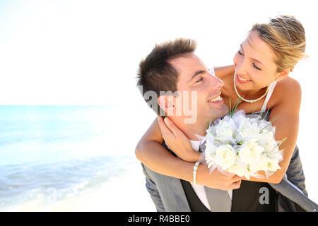Groom giving piggyback ride to his bride - Stock Photo