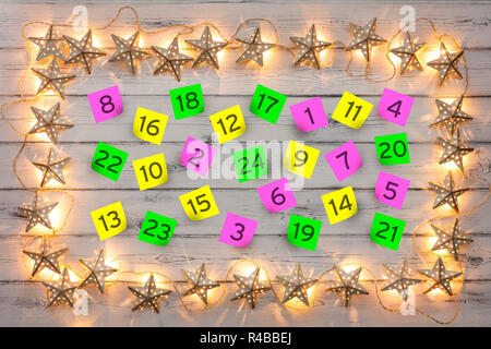 Advent numbered parer notes, with a border of golden star christmas lights, on a distressed white wooden board - Stock Photo
