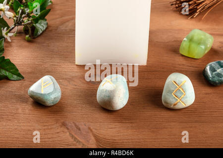 A closeup of Norse runes, stones with symbols used in Wicca and other magic and for divination, with a candle and crystals on a dark rustic background - Stock Photo