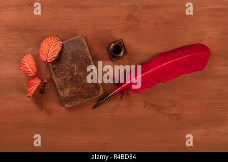Autumn Poetry. A photo of an old book with a thorny branch with vibrant leaves, an ink well, and a quill, shot from above on a dark wooden background - Stock Photo