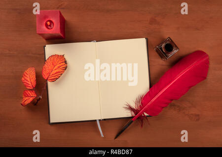 Fall Poetry. A photo of an open notebook with a thorny branch with vibrant leaves, an ink well, a quill, and a lit candle, shot from the top - Stock Photo