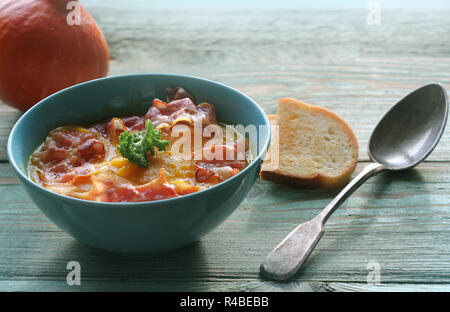 Pumpkin soup served with crispy bacon - Stock Photo