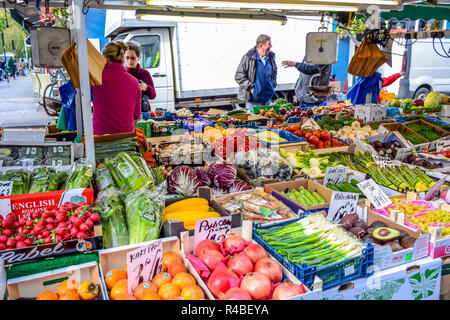 People buying fruits and vegetables at market stall in Portobello Road Market, Notting Hill, London, England, United Kingdom - Stock Photo