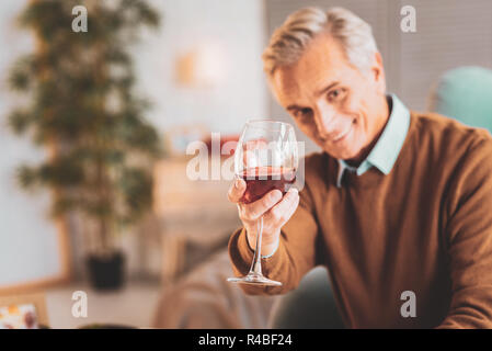 Glass of wine. Respectful man holding glass of nice French red wine in his hands sitting in living room - Stock Photo