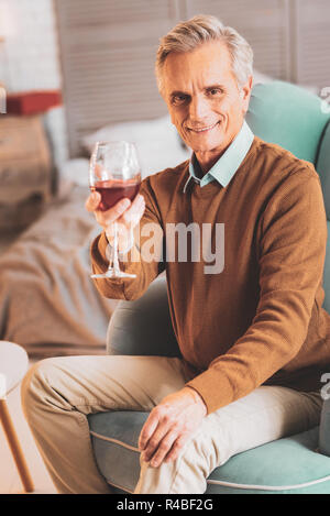 Caring man. Loving caring man feeling memorable while giving glass of wine to his beautiful wife - Stock Photo