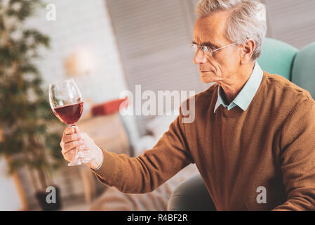 Wine expert. Professional wine expert feeling engaged in looking at glass of nice red wine - Stock Photo