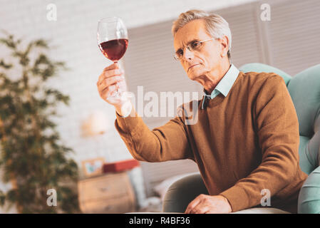 Experienced sommelier. Experienced professional sommelier feeling inspired while checking delicious French red wine - Stock Photo