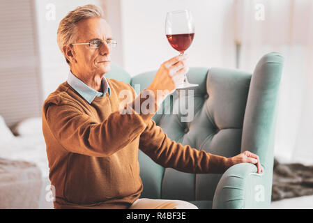Wine expert. Retired professional wine expert feeling memorable while drinking tasty red wine sitting at home - Stock Photo