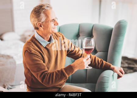Drinking wine. Loving husband feeling respected while drinking tasty wine with his caring family - Stock Photo
