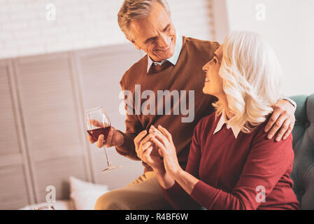 Elderly couple. Happy elderly couple of pensioners feeling joyful while drinking red wine together - Stock Photo
