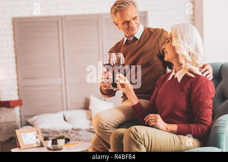 Clanging glasses. Couple of happy smiling pensioners clanging their glasses of wine wile enjoying evening at home - Stock Photo