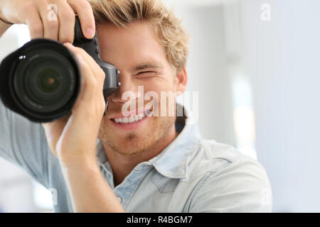 Fashion photographer shooting model in studio - Stock Photo