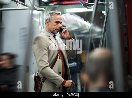Mature businessman with smartphone travelling by subway in city. - Stock Photo