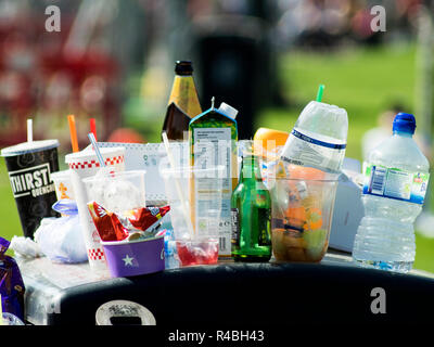 A rubbish bin overflowing with all kinds of trash and litter. - Stock Photo