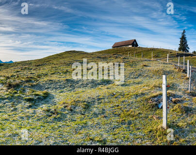 open country landscape with grassy meadow and rime and ice and old wooden fence in the middle under an expansive sky and a wooden hut up on the hill - Stock Photo