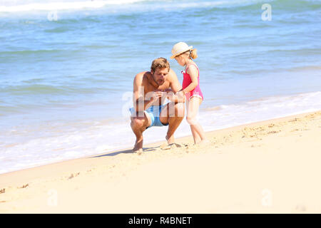 Daddy with little girl playing on the beach - Stock Photo